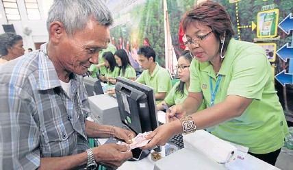 ?? PATIPAT JANTHONG ?? A rubber farmer in Nakhon Si Thammarat receives money from a bank clerk yesterday. He is among the first batch of 2,043 rubber growers in the province to receive the 2,520-baht-per-rai subsidy under government measures to help farmers shoulder...