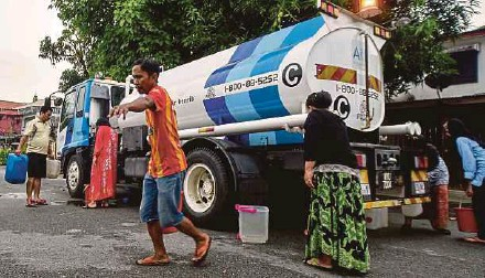 ?? PIC BY MUHAMMAD SULAIMAN ?? Residents collecting water from a tanker in Shah Alam yesterday.