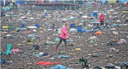 ?? Picture: BEN BIRCHALL / PA, MATT CARDY / GETTY ?? A Glastonbury festivalgoer navigates through the tons of rubbish, discarded tents and chairs yesterday