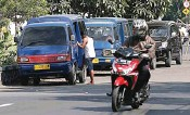 ?? GUSLAN GUMILANG/JAWA POS ?? CARI PENUMPANG: Angkutan umum parkir di bundaran Margomulyo. Dishub menegaskan akan melakukan penertiban.
