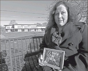 ?? Dale G. Young / The Detroit News ?? Kristy Loomis says she was abused as a child in Carson City by members of the Church at Carson City. Loomis holds a picture of her with her mother and brothers in 1997 in Carson City.