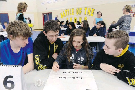 ?? DON HEALY/Leader-Post ?? Tyler Nagy, Jared Graham, Kiera Hamel and Evan Brick, all in Grade 8 from St. Gabriel school, participate in the city finals of the Regina Catholic School Division's Battle of the Books at Miller High School Tuesday. The student teams faced off over...