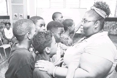 ?? GLADSTONE TAYLOR/PHOTOGRAPHER ?? Claudette Pious of the non-government organisation, Children First, raps with participants in the recent Bashy Bus Crew Summer Camp Programme held at the Kingston Technical High School in collaboration with the Kingston Central Police Division.