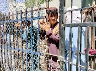 ?? (Anadolu via Getty) ?? Afghan peop l e wait at a border crossing to enter Pakistan