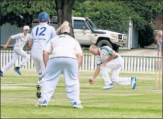 ?? PHOTOS: Paul Martin ?? SCOOP: Delatite C grade fielder Rohan Berriman scoops up a ball hoping to beat the City Colts batsman and get a run out.