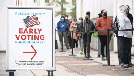 ?? JESSICA MCGOWAN/GETTY IMAGES ?? Georgians line up to vote in Atlanta in December's Senate runoff election.