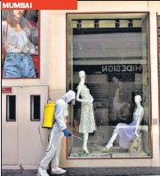 ?? PTI; BACHCHAN KUMAR/HT PHOTO ?? A man marks a shop after Delhi government announced reopening of local markets on an odd and even basis in New Delhi; a worker sanitises a mall in Navi Mumbai, on Sunday.