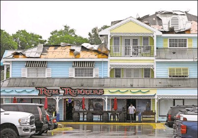 ?? Photos by CHRIS URSO | Times ?? Strong winds ripped portions of the roof off of Rum Runners Bar at the Key West Center in Palm Harbor on Sunday. Flooding was reported and power lines were downed around the area after severe thunderstorms passed through.