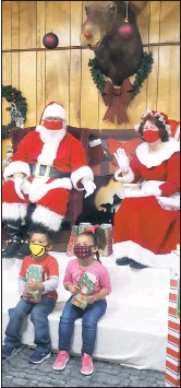 ?? HANNAH COMBS ?? Excited to see Santa and have their picture taken, Kadien Jones, 4, and Gabriella Greene, 3, enjoy spending time at the Queenstown Moose Lodge on Saturday, Dec. 12.