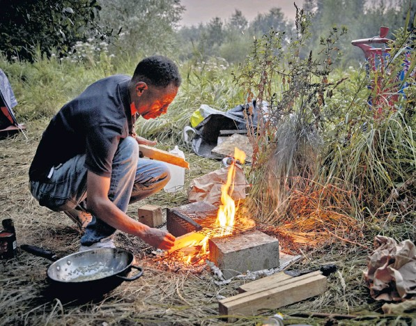 ??  ?? A migrant cooks on a small fire in a makeshift camp in wasteland on the outskirts of Calais. Recent evictions by French police at previously established camps have forced people to move to more remote areas. Left: migrants were spotted taking selfies as they waited to be rescued from an overloaded dinghy in the Channel