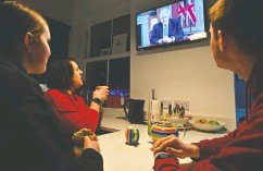 ?? PAUL ELLIS / AFP via Gett y Imag es ?? A family gathers around the telly in Liverpool to watch Prime Minister Boris Johnson give a message to the nation from 10 Downing Street on Monday.