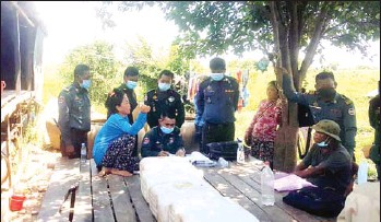 ?? FACEBOOK ?? Officers question villagers as they probe deaths from wine poisonings in Pursat's Krakor district.