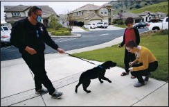 ??  ?? Dog trainer Joby Hurst introduces Molly and Matthew Ouimet, 18 and 10, to their Labrador companion dog Winnie recently at the Ouimets' Antioch home.