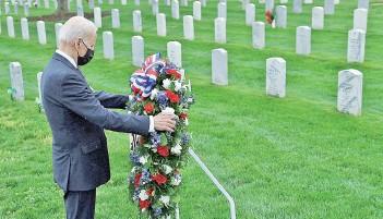 ?? — AFP photo ?? Biden lays a wreath in Arlington National cemetary to honor fallen veterans of Afghan conflict in Arlington, Virginia.
