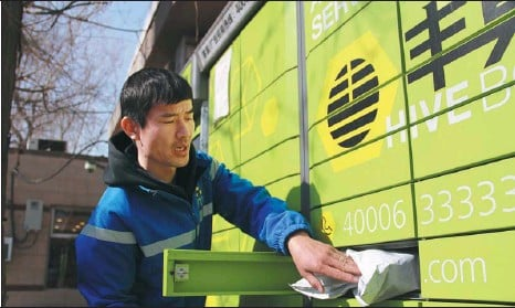 ?? ZHAO YIMENG / CHINA DAILY ?? Courier Chen Bin places a parcel inside a Hive Box locker at a residential community in Beijing's Dongcheng district on Feb 10.
