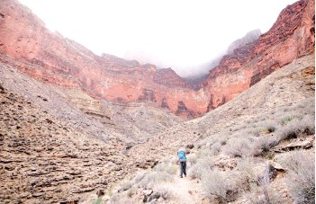 ?? — The Washington Post photos ?? John Briley's son Kai hikes along the Tonto Trail on the third day of their early March backpacking trip as mist spills off the South Rim of the Grand Canyon far above.