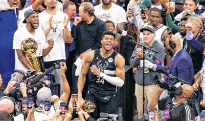 ?? JEFF HANISCH • USA TODAY SPORTS ?? Milwaukee Bucks' Giannis Antetokounmpo celebrates with the NBA Finals MVP Trophy following the game against the Phoenix Suns following Game 6 of the 2021 NBA Finals at Fiserv Forum in Milwaukee on Tuesday night.