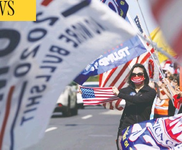 """?? ALEX EDELMAN / AFP VIA GETTY IMAGES ?? Supporters of U.S. President Donald Trump hold signs and flags on Sunday outside of Walter Reed Medical Center in Bethesda, Md., hoping to relay """"positive energy"""" to Trump as he battles the coronavirus."""