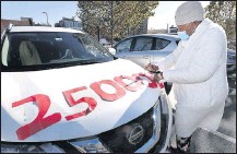 ?? ALEXA WELCH EDLUND/ TIMES-DISPATCH ?? Hilda Perkins puts cutouts on her car to recognize COVID-19 deaths in the U.S. before the Poor People's Campaign drive around the Capitol.