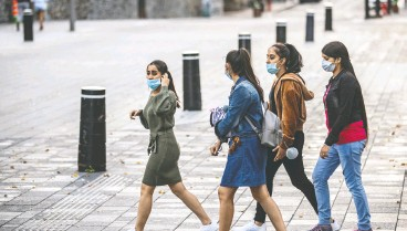 ?? Dav e Sidawa y / Montreal Gazett e ?? Montrealers continue to wear masks, including these young women crossing Notre Dame Street at Place d'armes on Thursday.