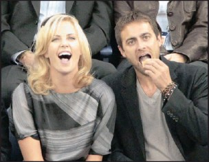 ?? Picture: KATHY WILLEN / AP ?? Theron, above and right, and her boyfriend, Stuart Townsend, attend the US Open tennis tournament in New York in September.'He rocks my world,' Charlize says.