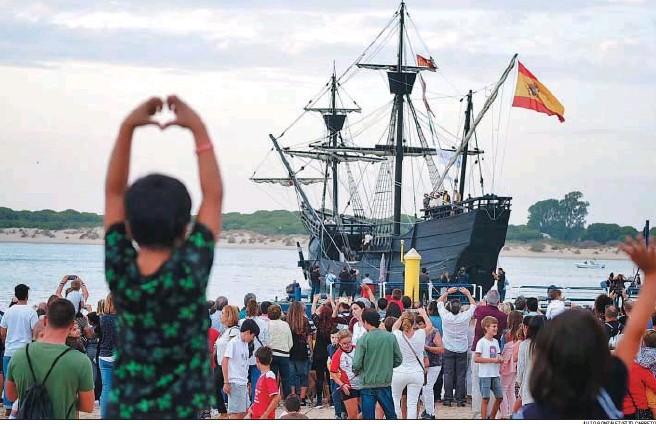 ?? JULIO GONZÁLEZ/FITO CARRETO ?? La réplica de la 'Nao Victoria' abandona el pantalán de Bajo de Guía ante la presencia de centenares de sanluqueños que quisieron despedirla desde la playa.
