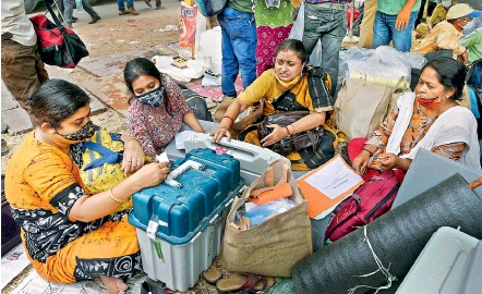 ?? PTI ?? Polling officials collect EVMs and other election materials before leaving for election duties for the 5th phase of West Bengal Assembly elections, at Bidhannagar in Kolkata on Friday. —