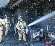 ?? The Sentinel-Record/Richard Rasmussen ?? ■ Hot Springs Fire Department firefighter Chance Estridge sprays water on an apartment that caught fire at 406 Oakcliff St. Wednesday.