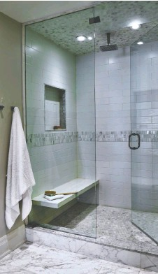 ??  ?? A shower with a rain shower head, bench and wall niche is a focal point of this bathroom by Kate + Co Design Inc.