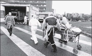 ?? THE ASSOCIATED PRESS ?? A patient infected with the coronavirus, coming from overcrowded hospitals in the Lyon region, is taken into the Hautepierre hospital in Strasbourg in eastern France. On Thursday, the surge of coronavirus cases showed signs of slowing in Germany and France.