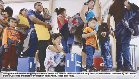 ?? AP ?? Immigrant families seeking asylum wait in line at the central bus station after they were processed and released by the United States Customs and Border Protection in McAllen, Texas on Friday.