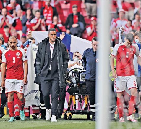 ??  ?? Paramedics take Eriksen off the pitch on a stretcher
