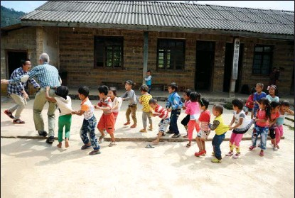 ?? PHOTOS PROVIDED TO CHINA DAILY ?? Michael Hermann, a humanitarian worker from Germany, has been a contributor and witness to the transformations in China's rural areas over the past few decades. During visits to far-flung regions, he actively engages with locals, including playing games with children.