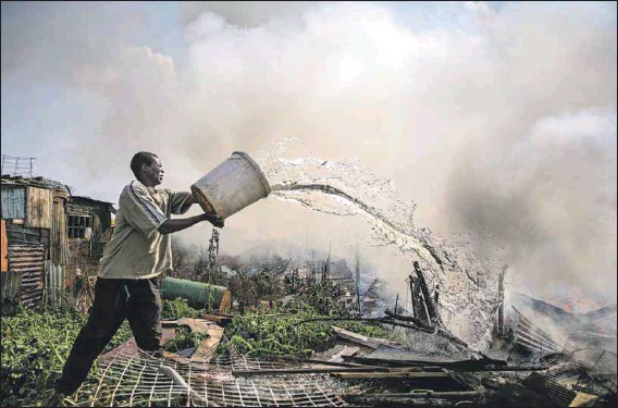 ?? Photo: Alon Skuy ?? The dangers of hate: A man fights the flames engulfing a shack in Ramaphosa settlement during the xenophobic violence in 2008.