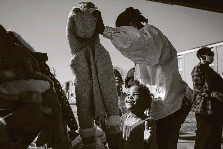 ?? Annie Mulligan / Contributor ?? Four-year-old Jaleah looks up at her new coat given by members of Community of Faith Church and Good Gang USA on Sunday at the Garden City Apartments in north Houston. Around 120 volunteers went to three sites to distribute coats.