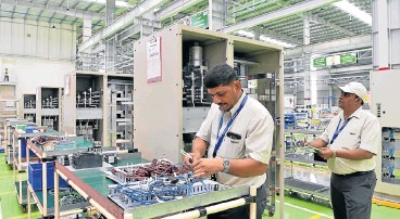 ?? /AFP Photo ?? Tech tests: Workers conduct product checks in the assembly area of a power electronics factory belonging to Toshiba Mitsubishi-Electric Industrial Systems in Tumakuru, about 100km from Bangalore.