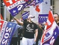 ?? Matt Slocum / Associated Press ?? PENNSYLVANIA: Trump supporters rally in Philadelphia outside the Pennsylvania Convention Center, where mail- in ballots are counted, slowly eroding the president's big lead.