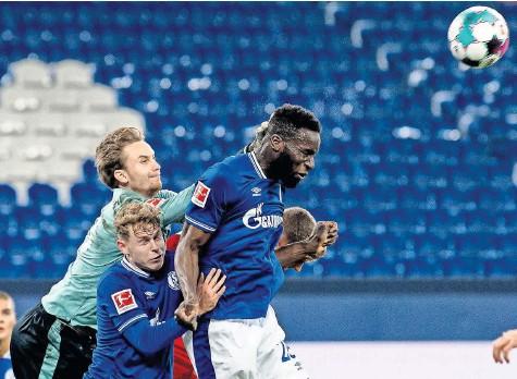 ?? Foto: Guido kirchner/dpa ?? Mit vereinten Kräften: Schalkes Torwart Frederik Rönnow (v. l.), Kilian Ludewig und Salif Sane holten den ersten Punkt.