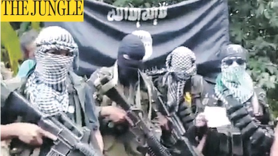 """?? AFP PHOTO / YOUTUBE"""" ?? While the kidnappers from Abu Sayyaf project the image of terrorists by utilizing ISIL flags, it is primarily theatrics meant to drive up their ransom demands."""