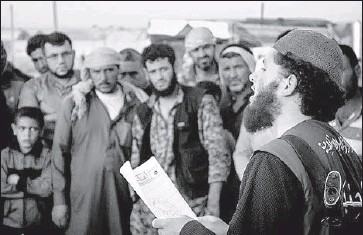 """?? Associated Press ?? A MEMBER of Islamic State's """"religious police"""" reads a verdict handed down by an Islamic court in Raqqah, Syria, sentencing accused adulterers to lashing. The photo was released last May by a militant website."""