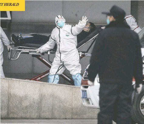 ?? GETTY IMAGES ?? Medical staff transfer patients to Jin Yintan hospital in Wuhan, China, on Jan. 17. Just weeks after a new pneumonia-like viral outbreak was first recognized in December, Chinese authorities began a dramatic lockdown of an entire city — and the world watched in horror.