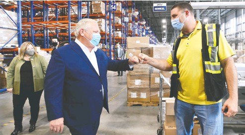 ?? Nathan Denette / THE CANADIAN PRESS ?? Ontario Premier Doug Ford, left, fist-bumps an employee as he tours a warehouse in Milton on Wednesday. Ford has not been nearly so confident about the state of the coronavirus in recent weeks, Randall Denley writes.