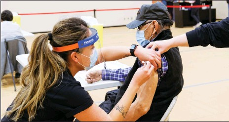 ?? Photos courtesy Siksika Health ?? Siksika Nation Elder Clement Leather receives his COVID-19 Vaccine from Siksika Community Health RN Angel Red Crow at the clinic Feb. 10.