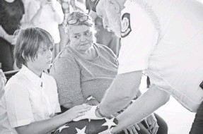 ?? MICHAEL A. SCHWARZ, USA TODAY ?? Stephen Akins' son, Skylar, and mother, Chrystal Akins, receive a flag from Doug Robbins, part of an American Legion Honor Guard, at the former soldier's funeral at Georgia National Cemetery on Julyly 9.