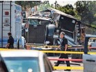 ?? DAMIAN DOVARGANES/AP ?? Officers walk past the remains of a Los Angeles Police Department tractor-trailer.