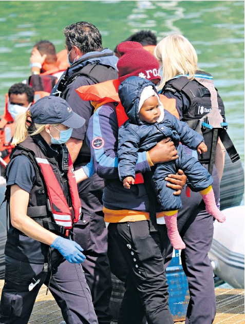 ??  ?? Migrants, including babies, arrive at Dover in Kent yesterday after being picked up at sea by Border Force vessels