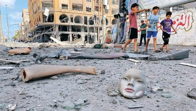 ??  ?? PARTS of a broken mannequin lie on the ground near a tower building which was hit by Israeli air strikes, amid a flare-up of IsraeliPalestinian violence in Gaza City yesterday.   Reuters