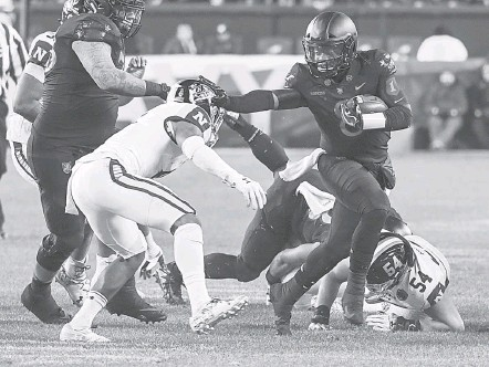 ?? JONATHAN NEWTON/THE WASHINGTON POST ?? Army's Kelvin Hopkins Jr. stiff-arms Navy safety Sean Williams in the third quarter. The quarterback led all players with 64 yards rushing.