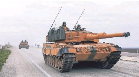 ?? FOTO: XINHUA/DPA ?? Ein türkischer Panzer vom Typ Leopard 2A4 des deutschen Rüstungsunternehmens Krauss-Maffei Wegmann fährt in der Nähe der syrischen Grenze.