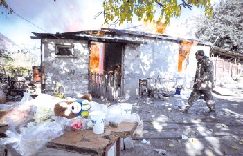 ?? — AFP photos ?? In this file photo taken on Nov 14, 2020 shows a man walks past as a house burns in the village of Charektar outside the town of Kalbajar, during the military conflict between Armenia and Azerbaijan.